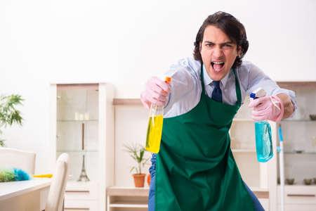 Jeune homme d'affaires nettoyant la maison