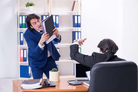 Jefe y su asistente masculino trabajando en la oficina. Foto de archivo