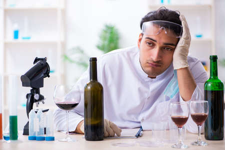 Male chemist examining wine samples at lab Фото со стока