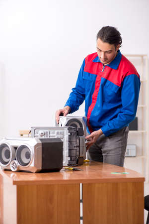 Young engineer repairing musical hi-fi system 版權商用圖片