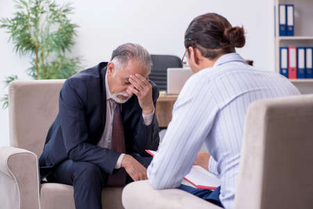 Old man visiting young male doctor psychologist