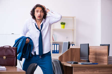Young male employee unhappy with excessive work Фото со стока