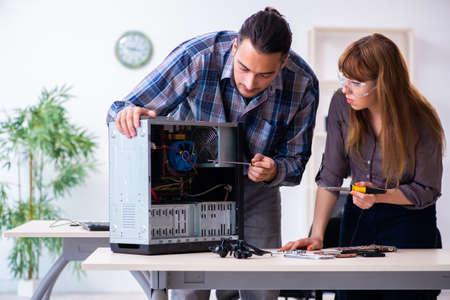 Two repairmen repairing desktop computer