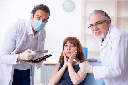Deux médecins de sexe masculin et jeune femme dans le concept de chirurgie plastique