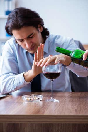 Männlicher Angestellter, der am Arbeitsplatz Alkohol trinkt und Zigaretten raucht