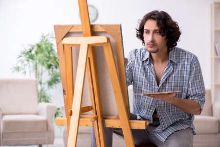 Young handsome man enjoying painting at home