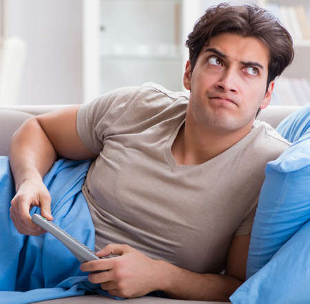 Man watching tv from bed holding remote control unit Banque d'images - 131886385