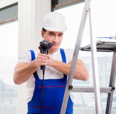 Repairman working with power drill in workshop Stock Photo