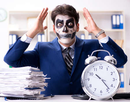 Businessman with scary face mask working in office 스톡 콘텐츠