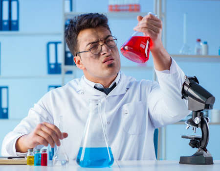 Funny mad chemist working in a laboratory 스톡 콘텐츠