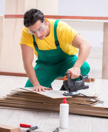 The contractor working on laminate wooden floor Zdjęcie Seryjne