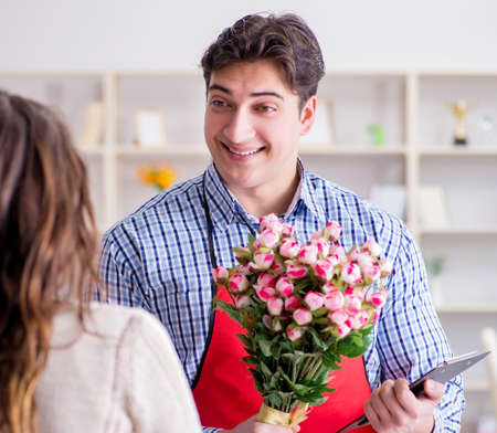 The flower shop assistant selling flowers to female customer