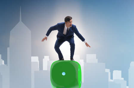 Businessman balancing on top of dice stack in uncertainty concept