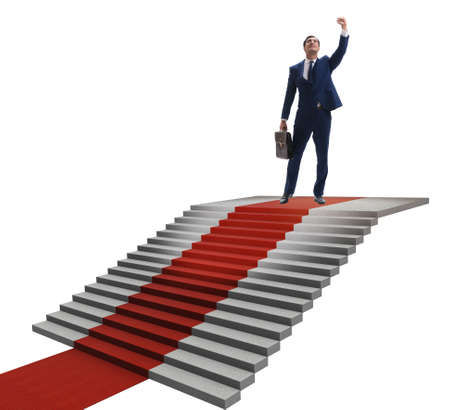 Young businessman climbing stairs and red carpet on white background 免版税图像