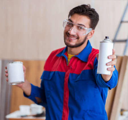 Young repairman carpenter working with paint painting Reklamní fotografie