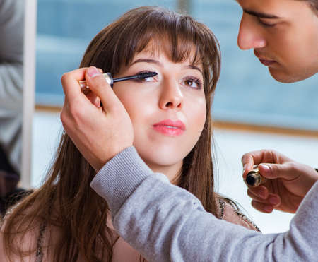 Man doing make-up for cute woman in beauty salon 스톡 콘텐츠