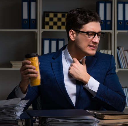 The employee working late and drinking strong coffee to stay away