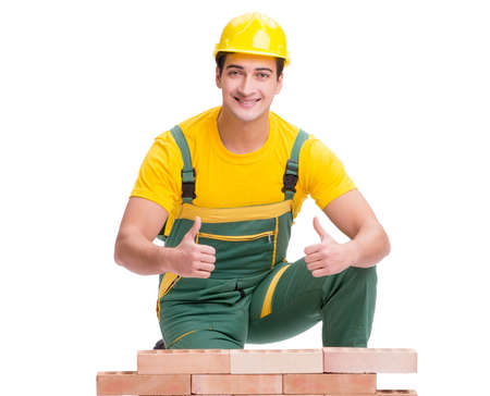 The handsome construction worker building brick wall