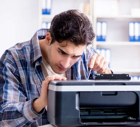 Hardware repairman repairing broken printer fax machine Stock Photo