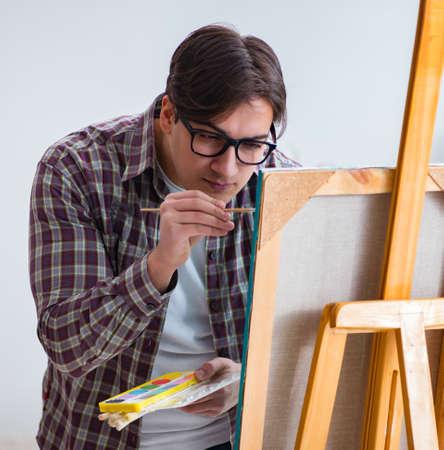 Junger männlicher Künstler, der Bilder im hellen Studio zeichnet
