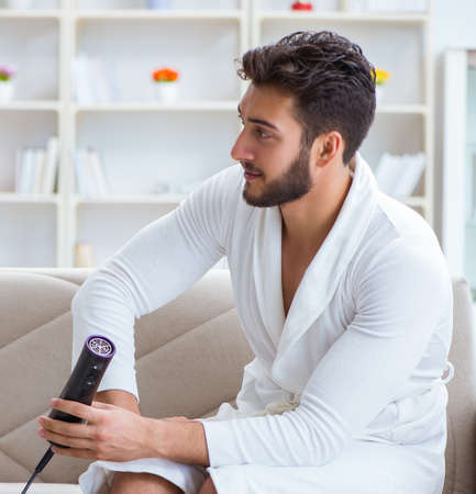 Young man drying hair at home with a hair dryer blower Imagens
