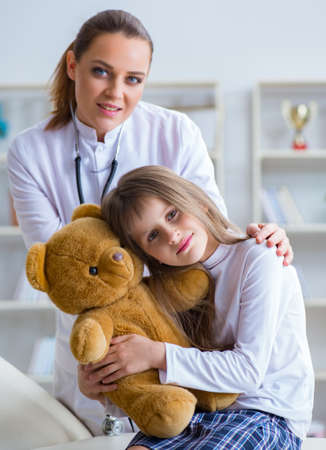 The woman female doctor examining little cute girl with toy bear