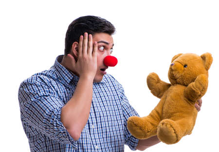 Funny clown man with a soft teddy bear toy isolated on white