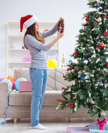 Single girl decorating christmas tree Stockfoto