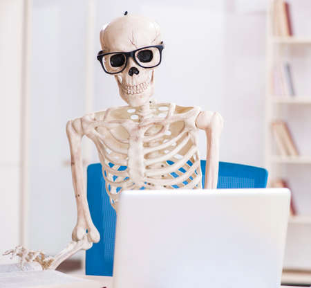 Skeleton businessman working in the office Imagens