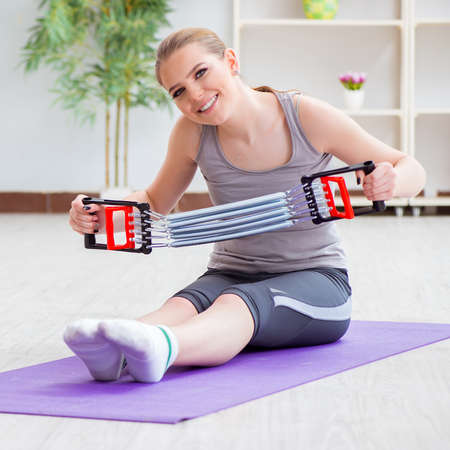 Young woman exercising with resistance band in gym