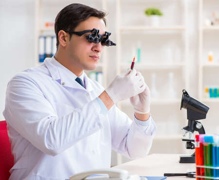 Doctor chemist working on blood samples in lab Imagens