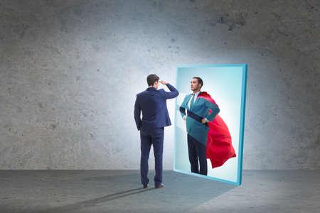 Businessman seeing himself in mirror as superhero 写真素材