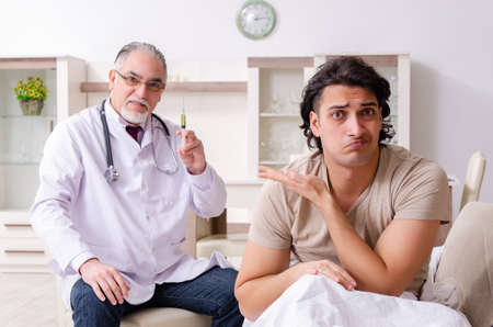 Old male doctor visiting young male patient Imagens - 131945484