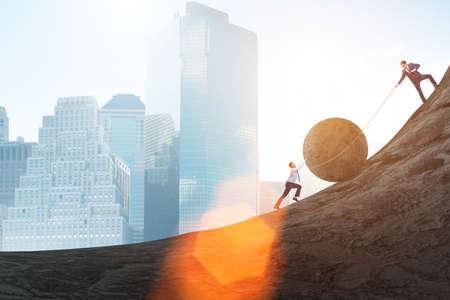 Teamwerkvoorbeeld met zakenmensen die steen naar boven duwen Stockfoto
