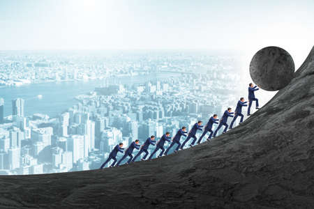 Team of people pushing stone uphill