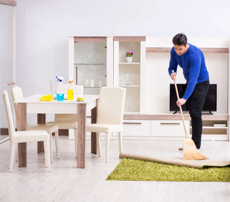 Young man cleaning floor with broom
