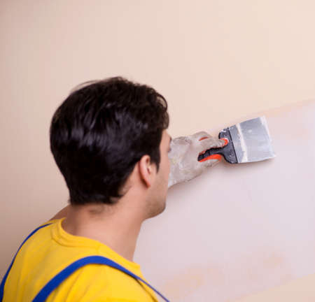 Young contractor employee applying plaster on wall Stock fotó