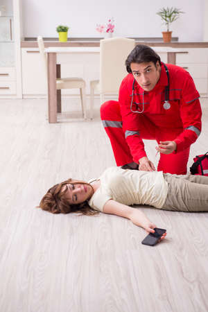 Young male paramedic visiting young woman 写真素材