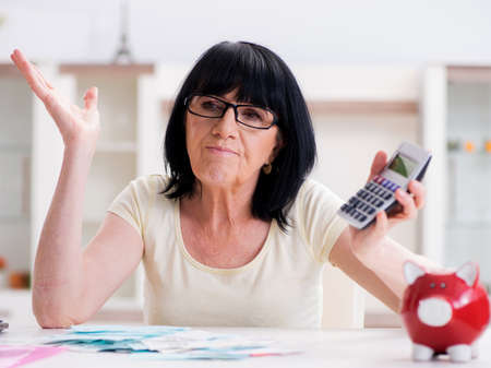 Mature woman trying to reconcile her bills