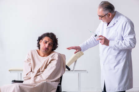Old male doctor psychiatrist and patient in wheel-chair Imagens
