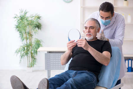 Old man visiting young doctor for plastic surgery 스톡 콘텐츠