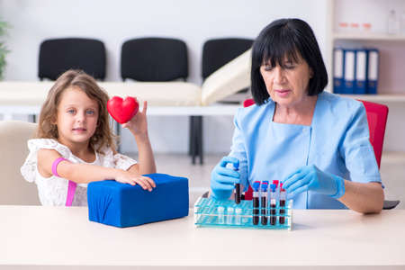 Little girl visiting old female doctor