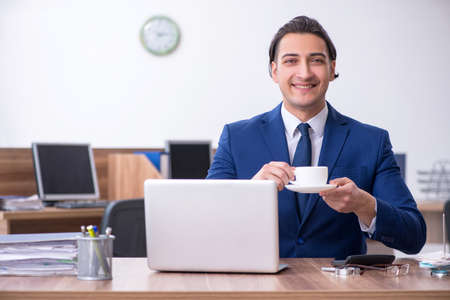 Young male businessman working in the office Foto de archivo - 132004900