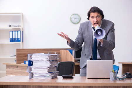 Young male employee unhappy with excessive work Imagens