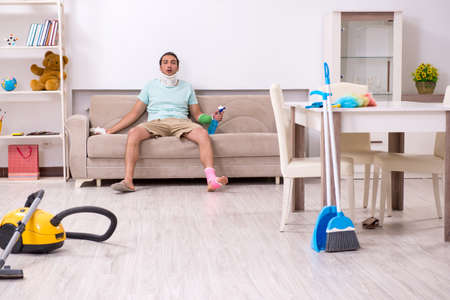 Young injured man cleaning the house