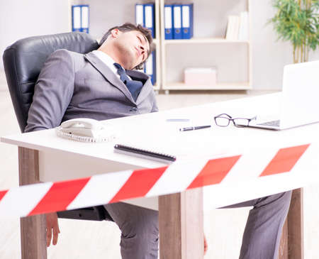 Dead businessman at this desk Stock Photo