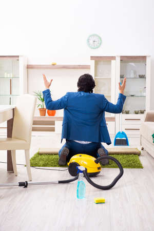 Young businessman cleaning the house Stok Fotoğraf