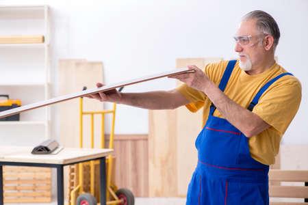 Old male carpenter working in workshop