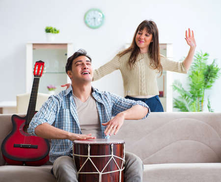 Young family singing and playing music at home Stok Fotoğraf - 132236404