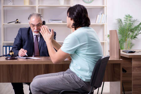 Young man visiting experienced male lawyer Stock fotó